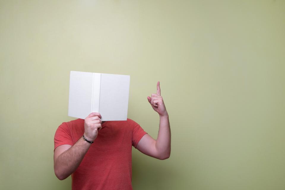 Fotografía de un hombre sosteniendo un libro y haciendo señal de indicación