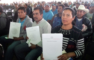 Beneficiarios levantan en sus manos sus escrituras y documentos agrarios.