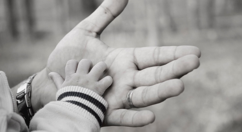 Un padre toma la mano de su hijo.