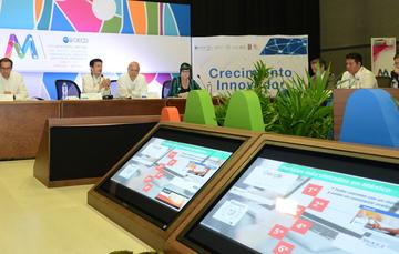 """Secretario Virgilio Andrade haciendo su presentación en el foro """"Gobierno Digital y Competitividad Empresarial"""", se ven en primer plano las pantallas con su presentación y al fondeo el explicando, a su lado los demás ponentes"""