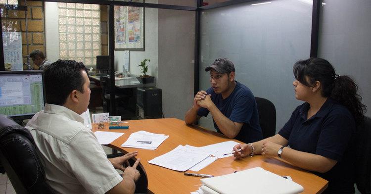 Una persona en un escritorio atendiendo a dos que piden informes sobre un sindicato.