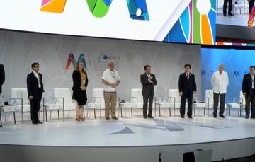 Secretario de la Función Pública dando mensaje de Clausura de la Reunión Ministerial de la OCDE 2016, al fondo pantalla dónde se ve él mismo y las personas del presidium