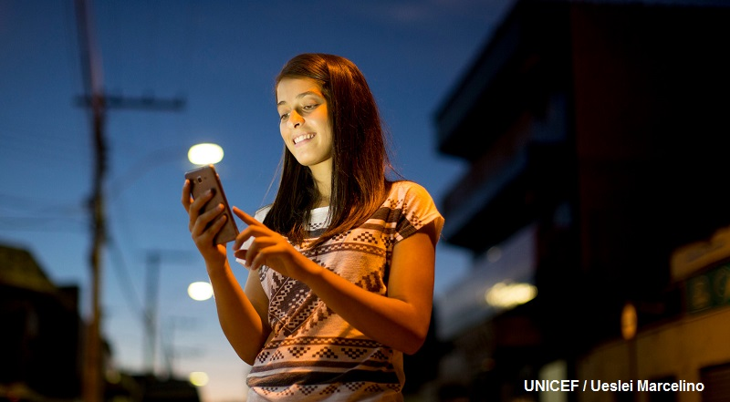 Chica adolescente de 16 años, sonriente, consulta sus redes sociales con su celular en la mano, en la calle cerca de su casa.