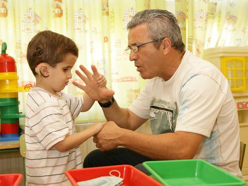 Niño sordociego se comunica a través del tacto con un adulto.