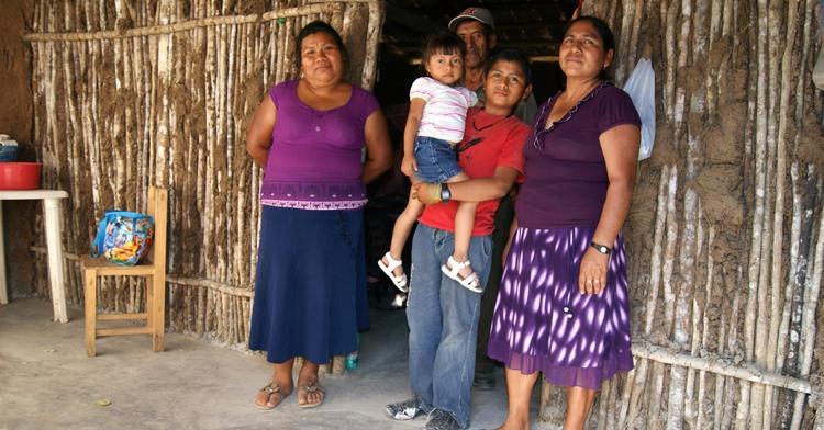 Familia de papá, mamá, un niño y una niña fuera de su casa.
