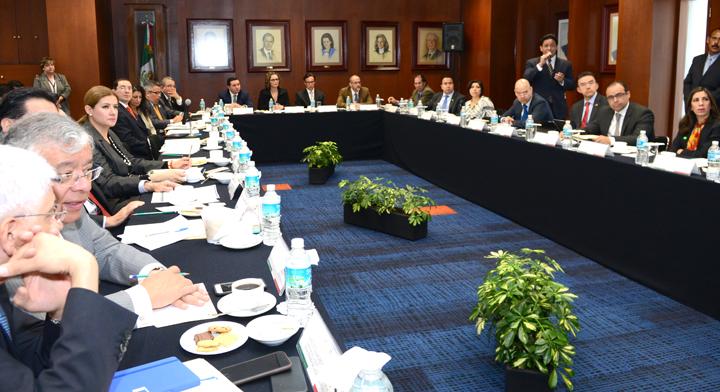 Reunión de Personas sentadas alrededor de  una mesa con forma de U invertida, en el centro se ven plantas y en las paredes pinturas de funcionarios