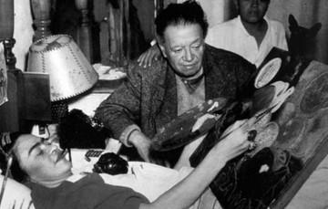 Frida Kahlo, pinta en un caballete adaptado mientras convalece en su cama, a un lado Diego Rivera observa.