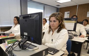 Grupo de cinco personas tomando capacitación en sus computadoras.