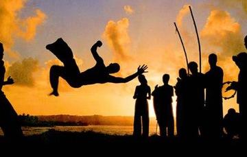 Jóvenes brasileños bailan capoeira.