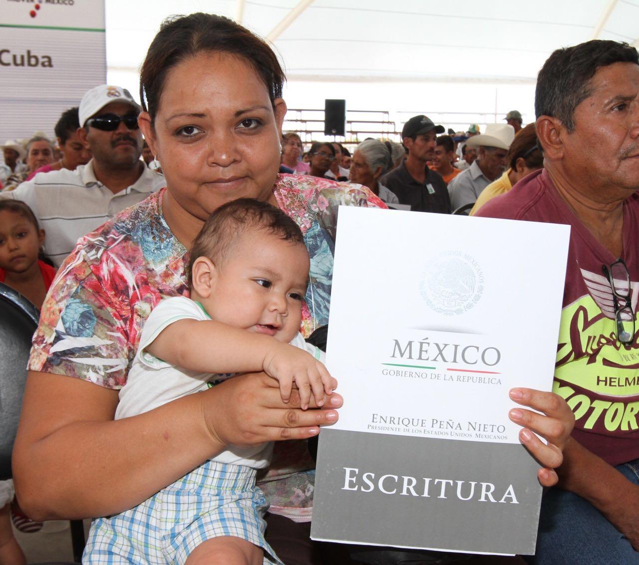 Madre de familia con su hijo en brazos sostiene su escritura de su vivienda, lo que le permite dejar un patrimonio a su familia.