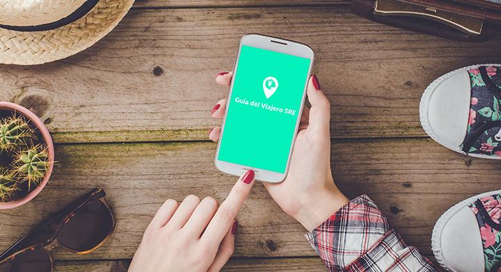 """En la imagen hay un teléfono inteligente con la app """"Guía del Viajero SRE"""" en la pantalla."""