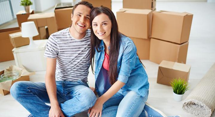 Una pareja joven en un departamento nuevo entre cajas de mudanza.
