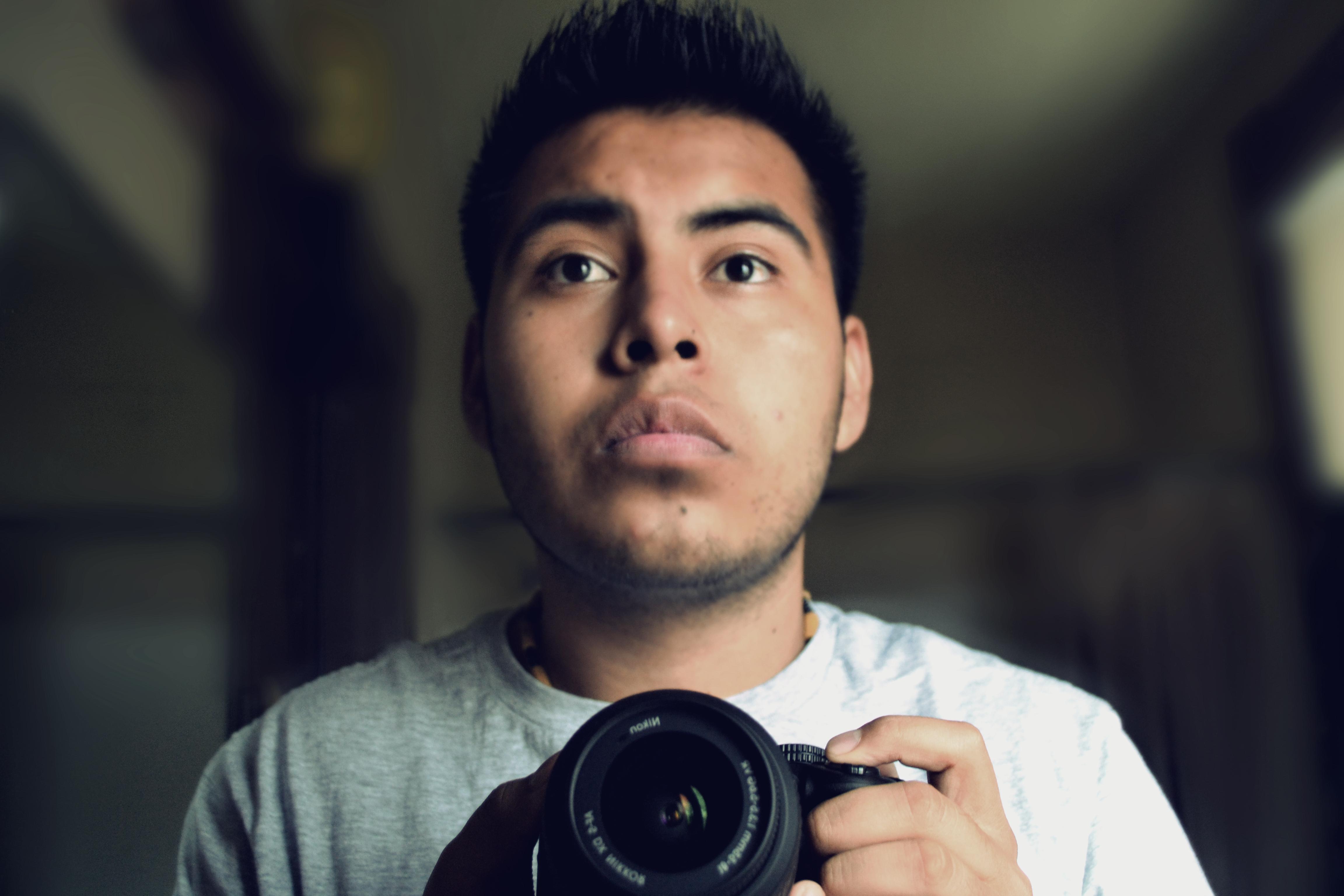 Joven mexicano con una cámara de fotos en las manos.