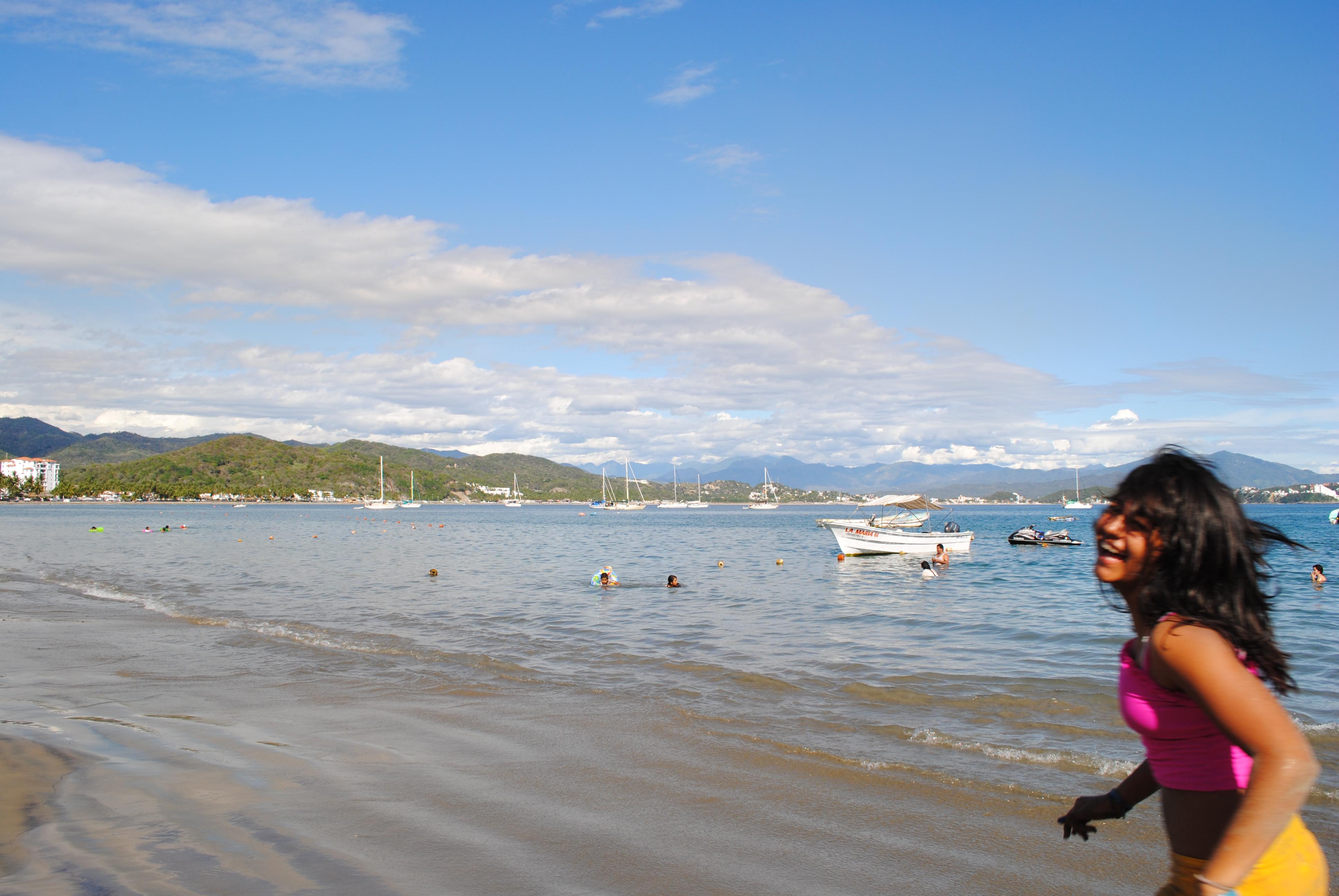 Una chica joven pasea en la playa.