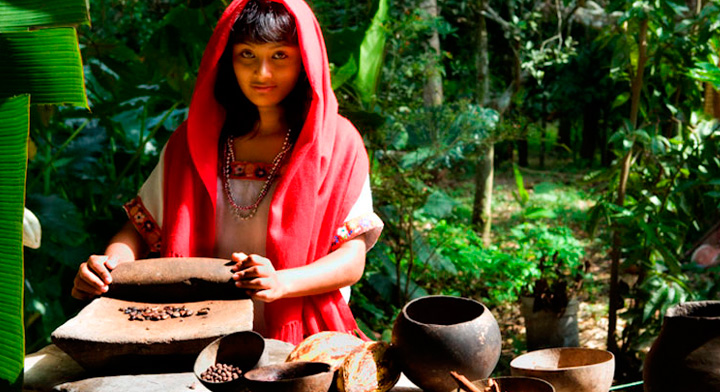 Mujer joven moliendo cacao
