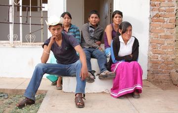 Dos hombres jóvenes y tres chicas jóvenes sentados al pie de una puerta
