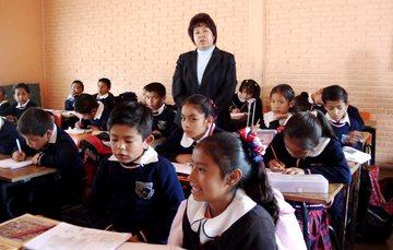 Salón de primaria con niños y niñas estudiando y su maestra