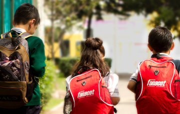 Niños caminando con sus mochilas vistos de espaldas en su regreso a clases.