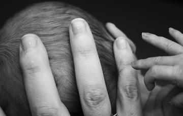 Bebé sostenido por la madre, con las manos en su cabeza.