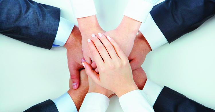 Varios hombres y mujeres unen las manos en señal de que trabajan en equipo.