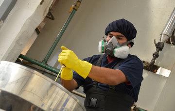 Hombre bien equipado con mascarilla, guantes y cofia, trabajando con químicos.