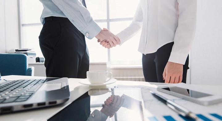Hombre y mujer dándose la mano en una oficina