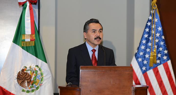 Mtro.  Javier Vargas Zempoaltecatl hablando entre las banderas de México y Estados Unidos