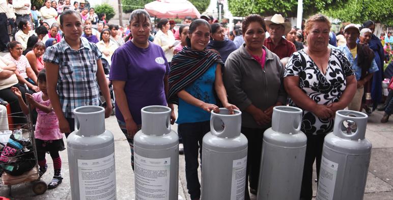 Mujeres de pie, y enfrente de ellas aparecen tanques de gas l.p.
