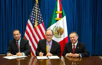 Tres hombres sentados frente a una mesa, dos de ellos firmando un documento. Los tres sonriendo, detrás de ellos las banderas de Estados Unidos y México.