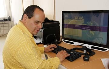 Hombre invidente trabajando frente a una computadora.