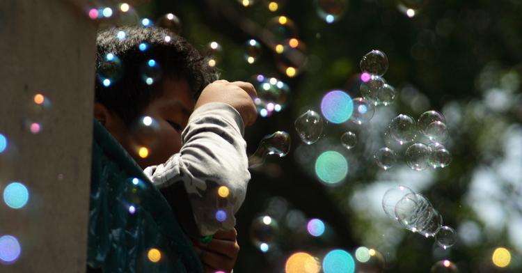 Imagen de un niño jugando a hacer burbujas de jabón.