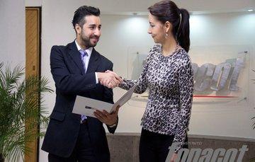 Un hombre y una mujer de pie saludándose. Mientras tanto el hombre le entrega un fólder con los papeles de su crédito FONACOT.