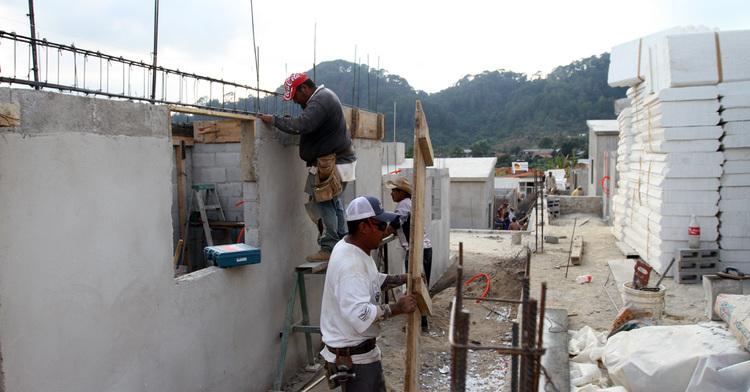 Trabajadores realizan la construcción de viviendas.
