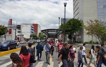 Fotografía de varias personas, algunas cruzando la calle y otras saliendo de una terminal de transporte público.