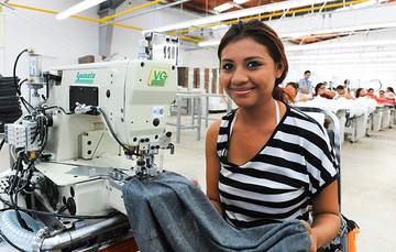Mujer trabajando en una máquina de cocer sentada, con una tela en la mano. Detrás de ella más personas trabajando.