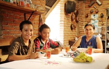 Familia de dos hijos y mamá comiendo en su casa