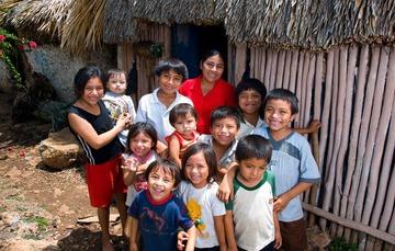 Niñas, niños y una joven sonriendo a la cámara en un área rural