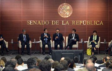 Javier Vargas, encargado del despacho, hablando en el centro del presidium, acompañado por otros servidores, todos sentados de frente al auditorio; a sus espaldas una pared con textura de madera, el escudo nacional y el texto: Senado de la República.