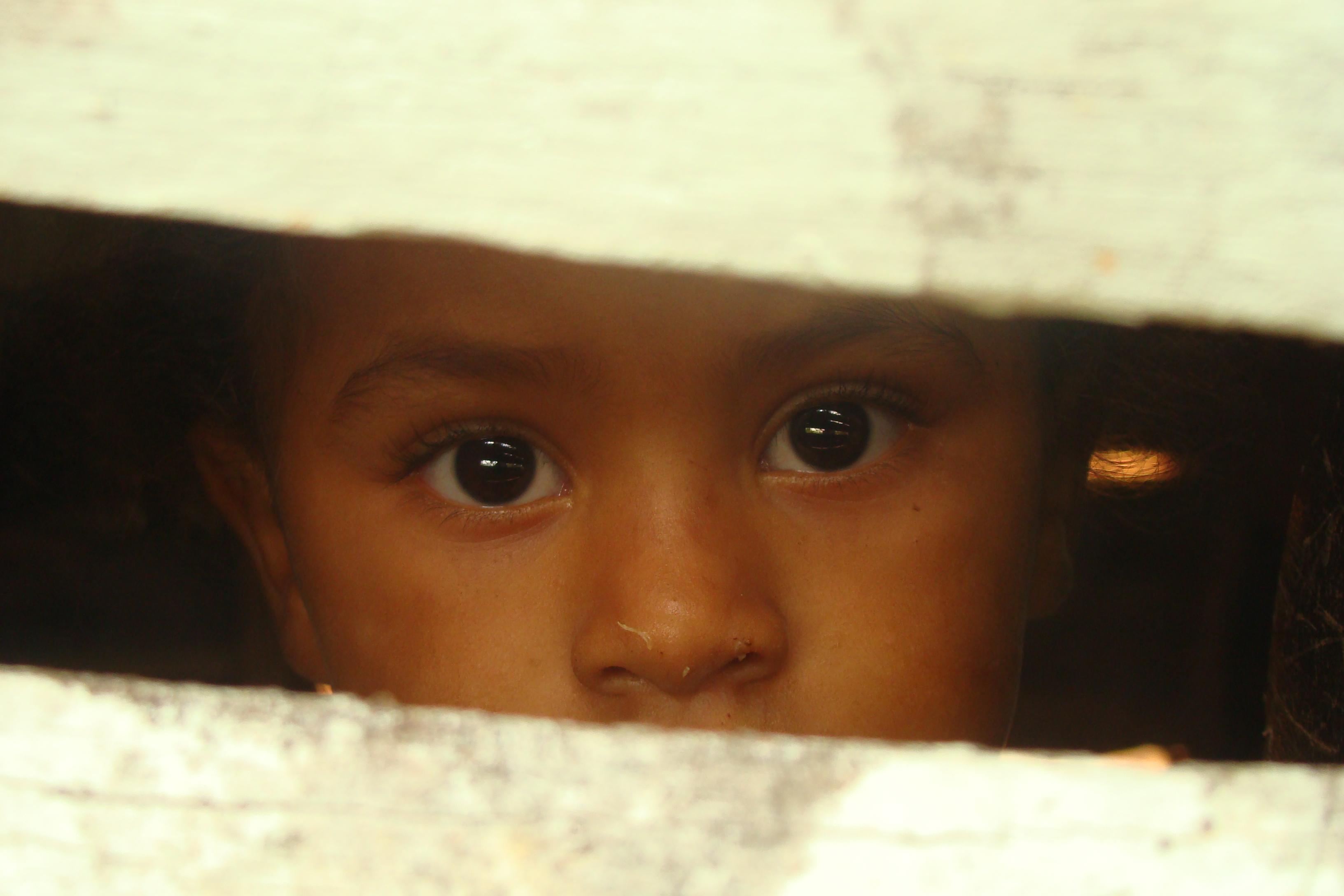 Una niña mira por la apertura de una puerta.