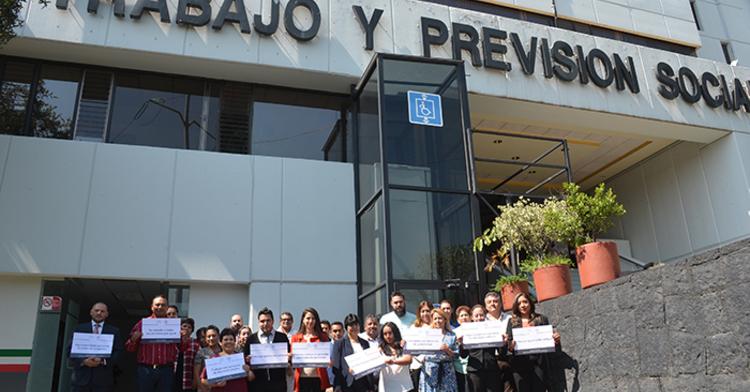Grupo de personas afuera de la STPS con carteles en contra de la discriminación.