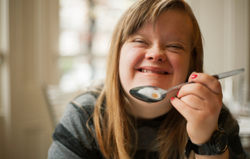 Chica con Síndrome de Down sonríe mientras sostiene una cuchara con comida