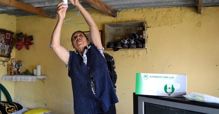 Señora colocando un foco ahorrador en su habitación