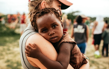 Una niña en brazos de una chica que la protege.