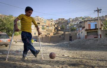 Niño con secuela de polio patea un balón de fútbol, apoyado en sus muletas canadienses