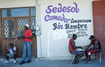 Comedor Comunitario en Mexicali, Baja California, 4 migrantes hombres en la puerta