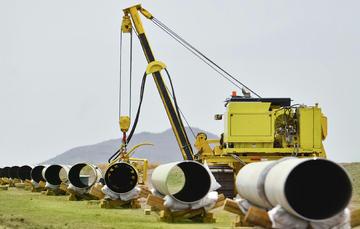 La imagen muestra una grúa acomodando tubos utilizados en los gasoductos.