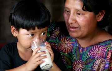 Una mujer con vestido típico mexicano con un niño pequeño que bebe un vaso de leche