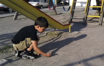 Niño hincado jugando canicas en un parque.