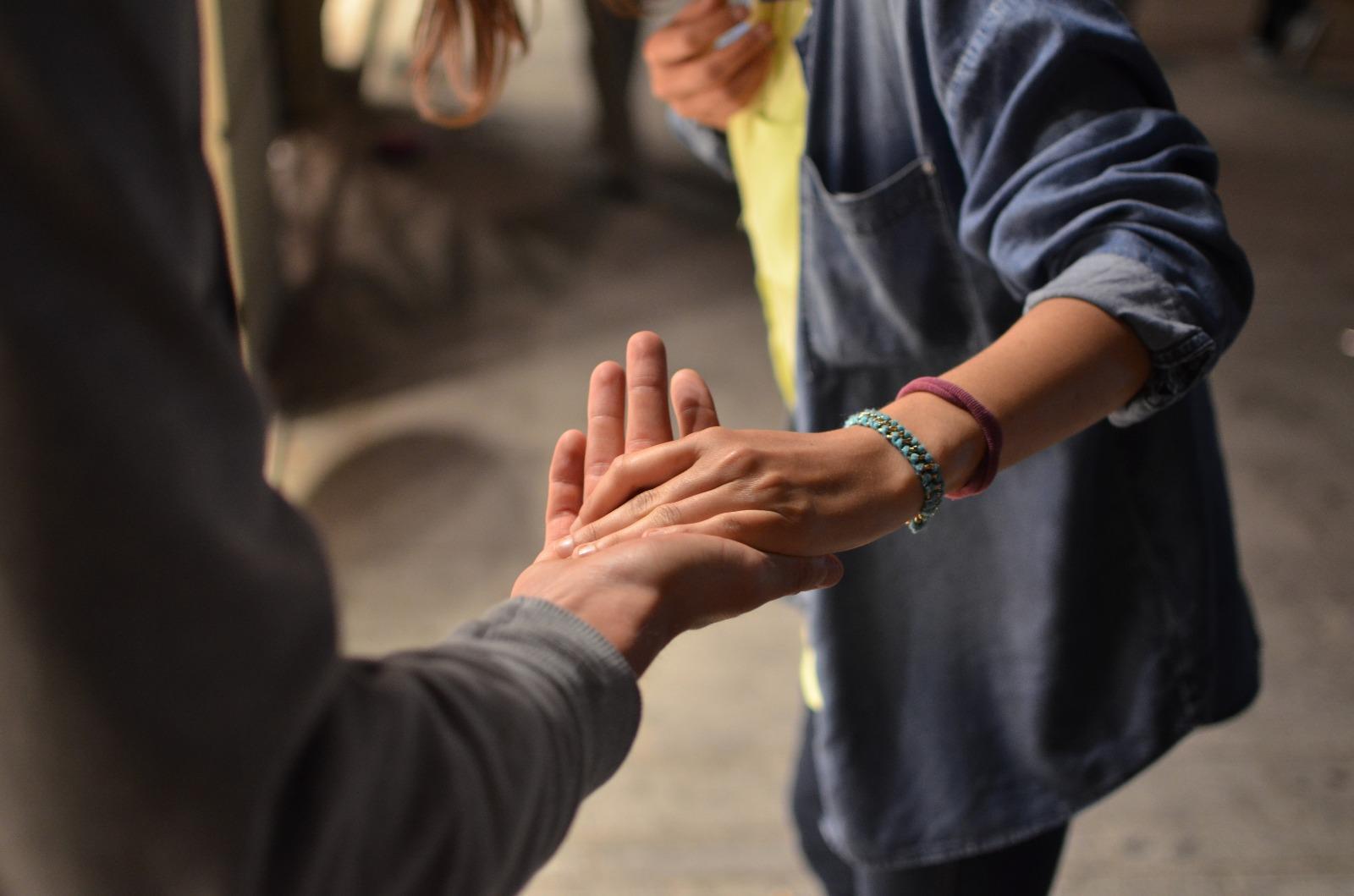 Dos personas se dan la mano.