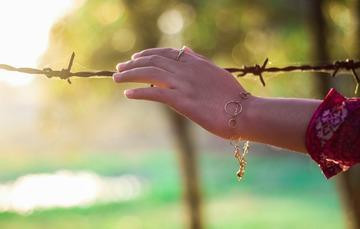Mano de una mujer cerca a una cadena de puas
